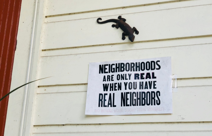 "Sign says ""neighborhoods are only real when you have real neighbors"" as a response to gentrification and AirBnB pushing out residents from the city"